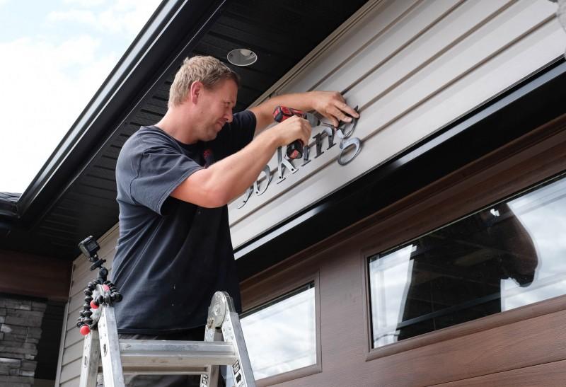 Derek installs signage.