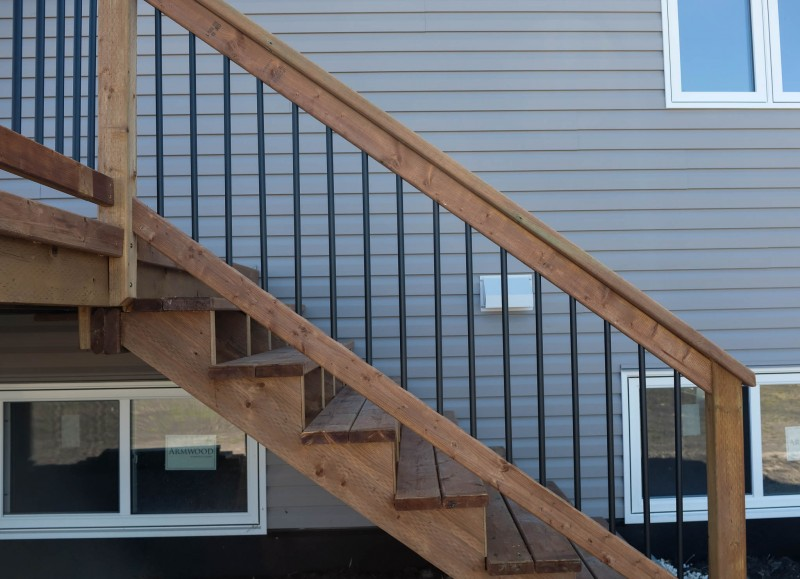 Brown treated stair railing with black ballusters.