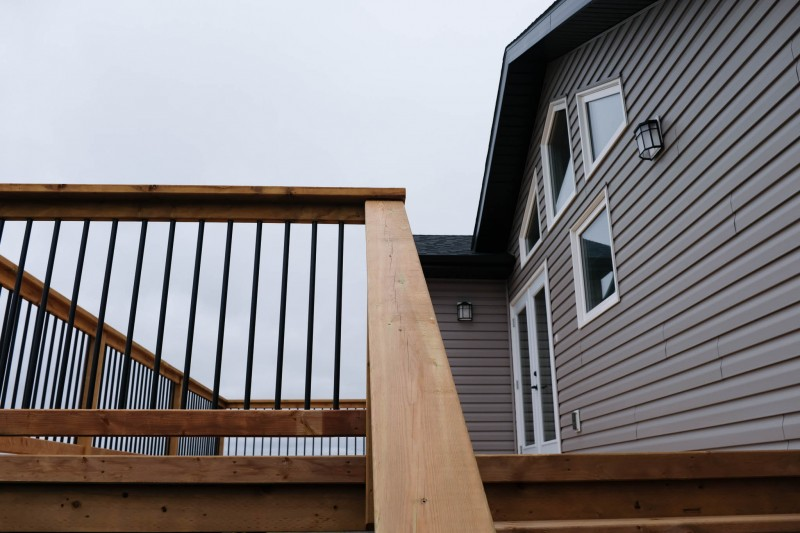Brown treated deck with black ballusters.