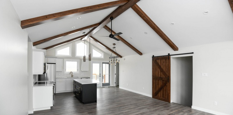 Faux beams with matching barn door in open concept floor plan.