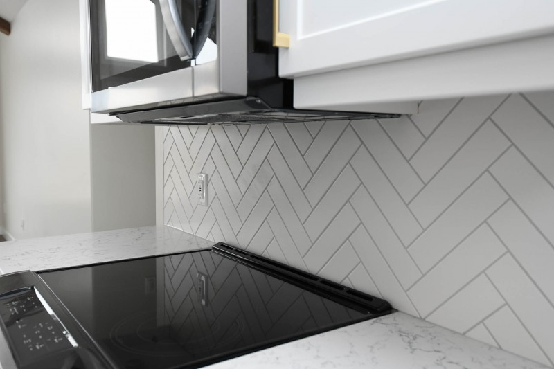Herringbone backsplash with slide-in stove.