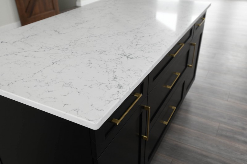 White Attica quartz counterop on black painted island cabinets with gold pulls.