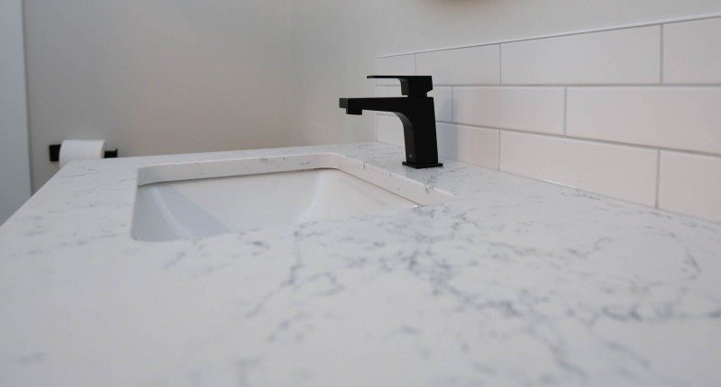 Quartz vanity countertop with undermount sink with black taps.