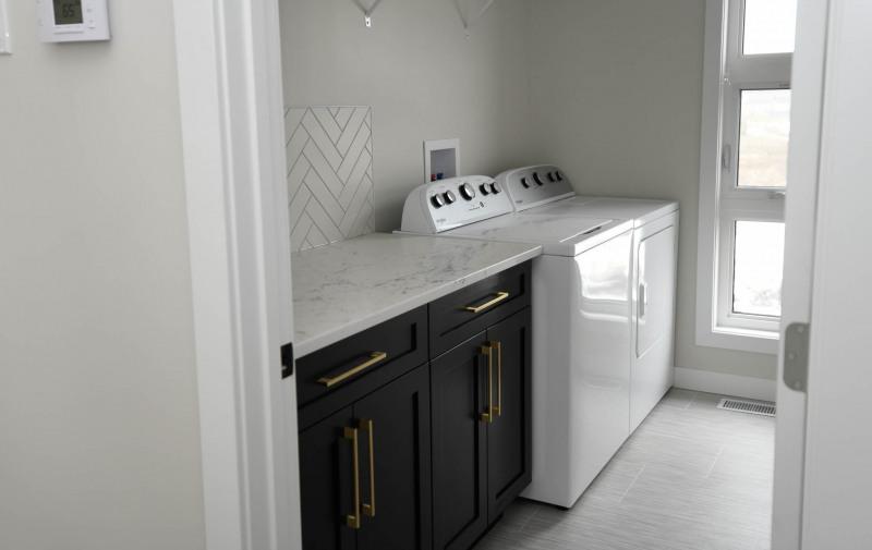 Laundry room with herringbone backsplash.