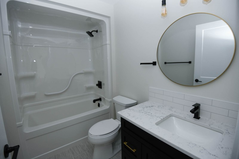 Main bathoom with black plumbing fixtures and gold mirror.